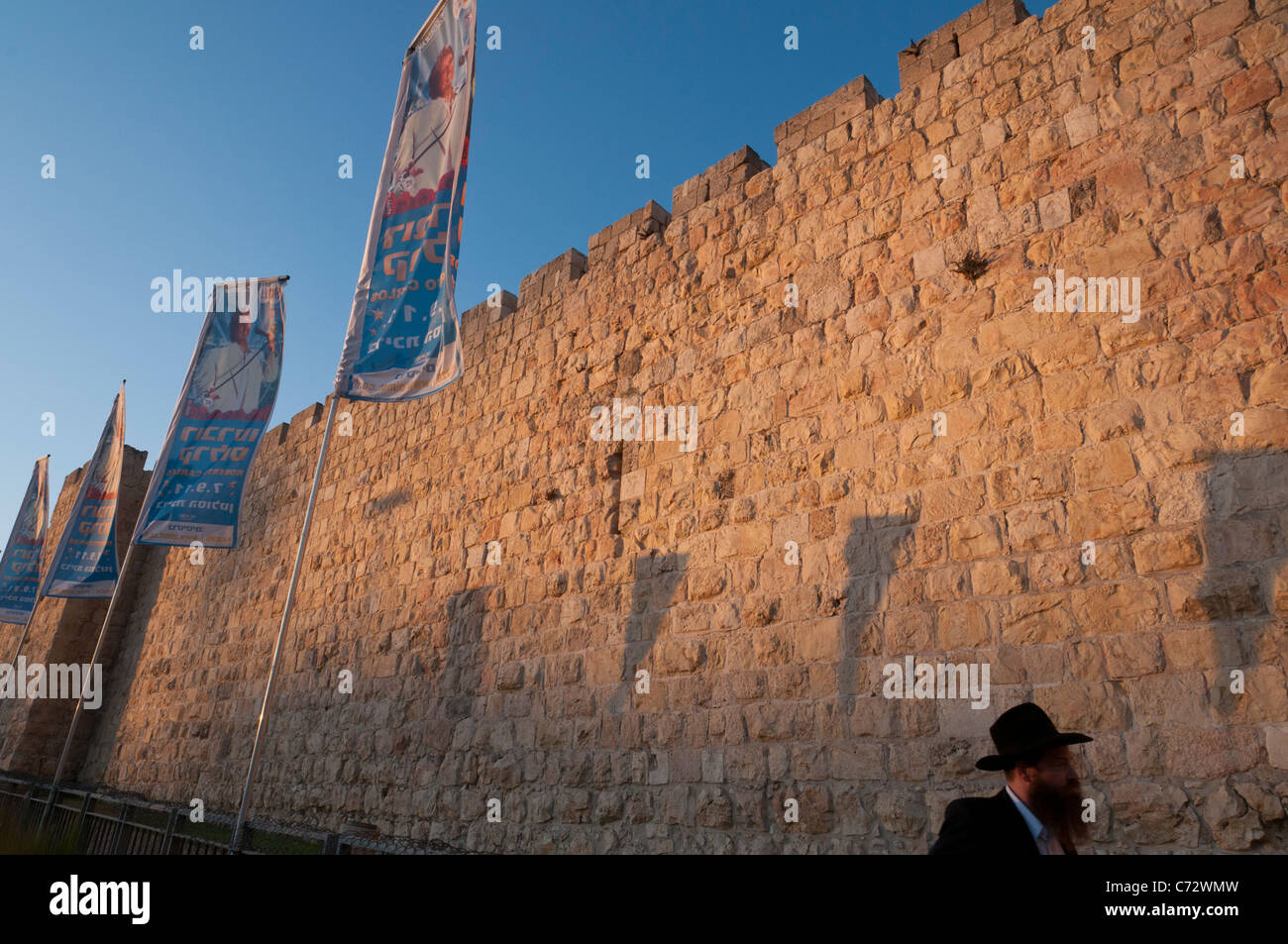 City walls at sunset with flags and orthodox jew. Jaffa Gate. Jerusalem Old City. israel - Stock Image