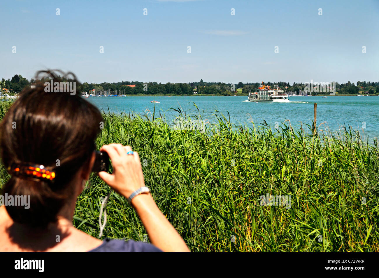 Woman taking a photo of a Chiemsee passenger ferry,Herrenchiemsee, Herreninsel Upper Bavaria Germany - Stock Image