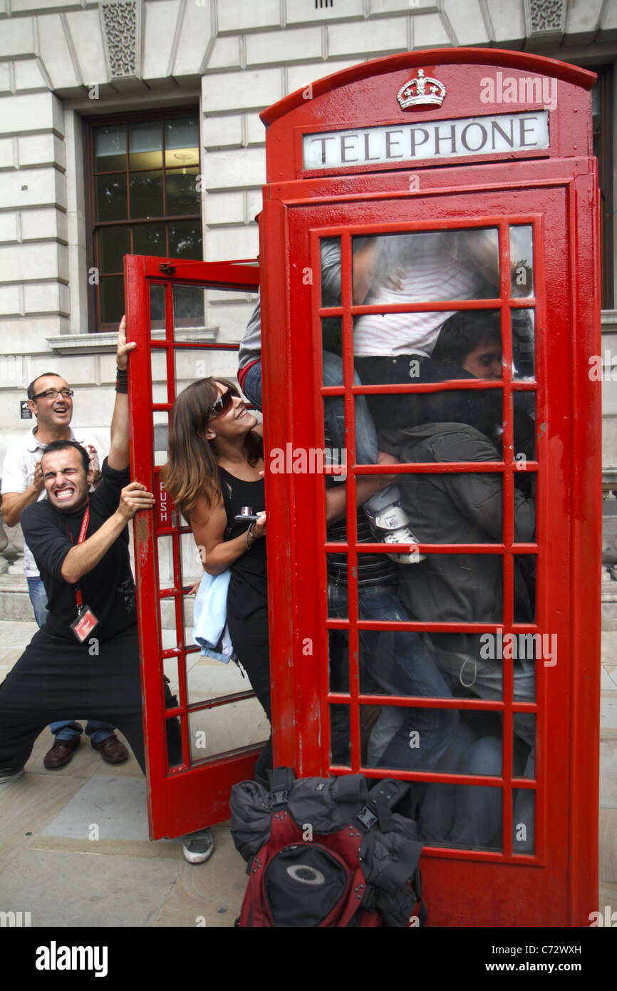 Tourists attempt to squeeze into telephone box, London, UK - Stock Image