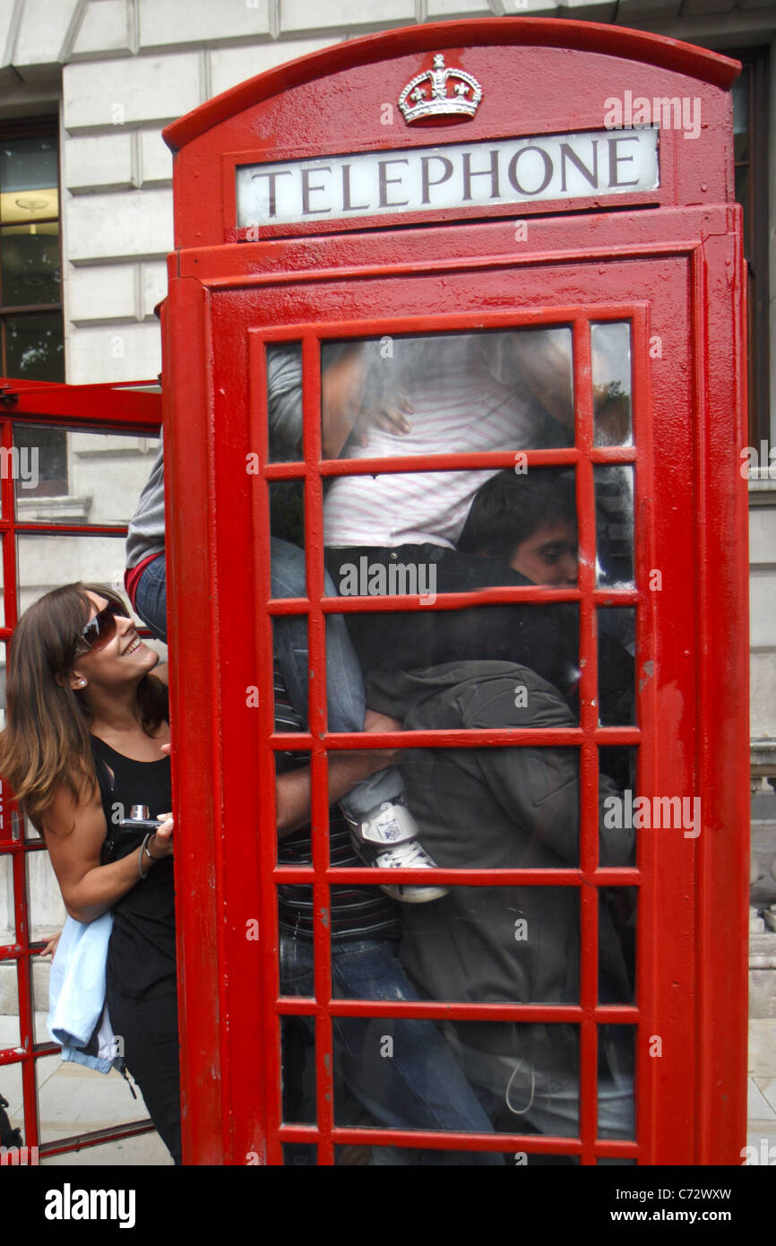 Tourists pack inside a telephone box, London, UK - Stock Image
