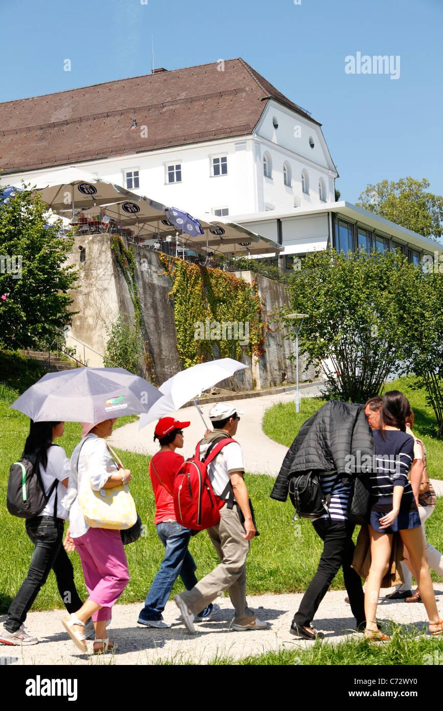 People walking past the Augustine Monastery,Herrenchiemsee, Herreninsel Upper Bavaria Germany - Stock Image