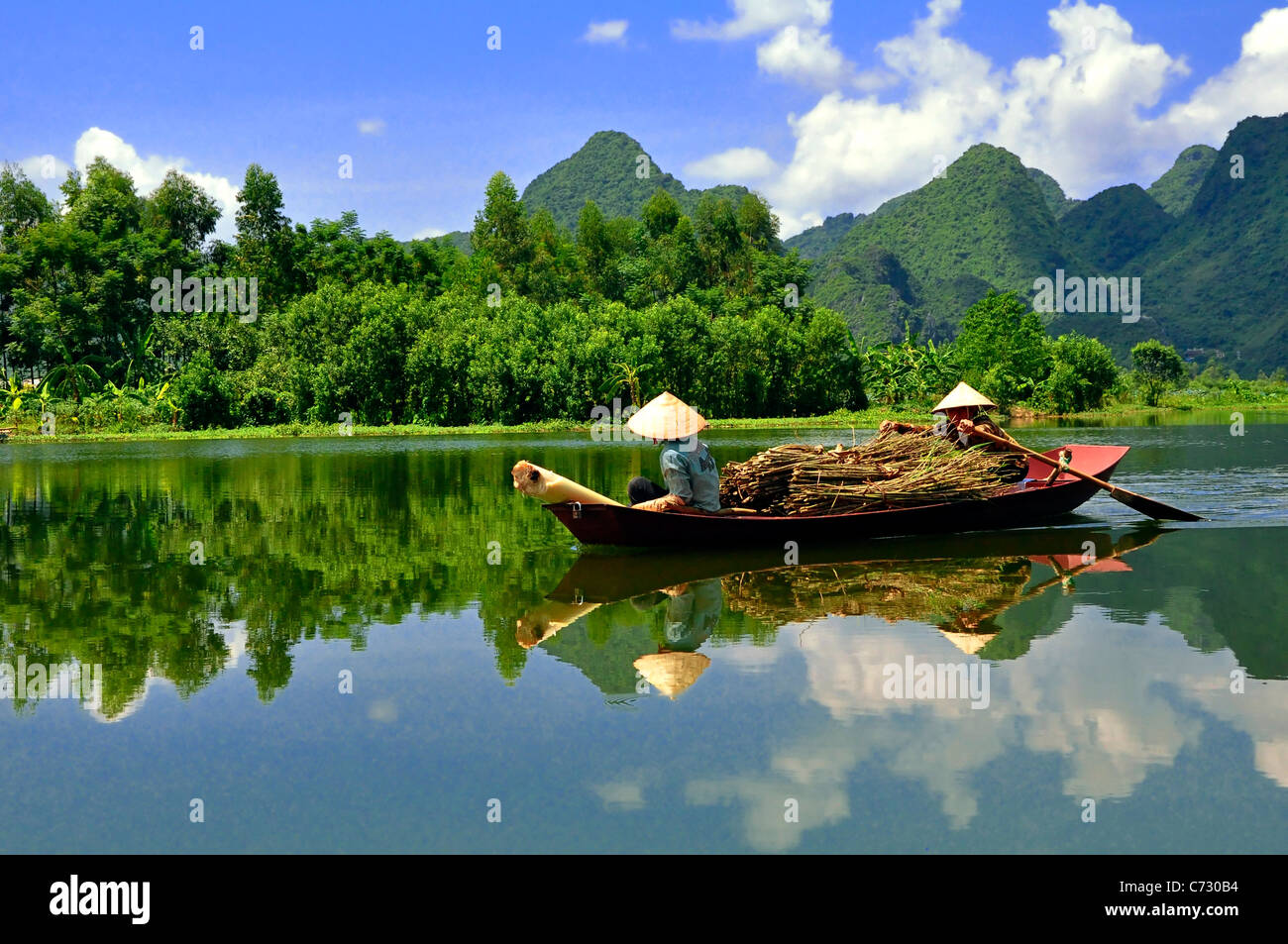 A photo of two boatwomen from Tam Coc, Vietnam bringing back firewood to the town. - Stock Image