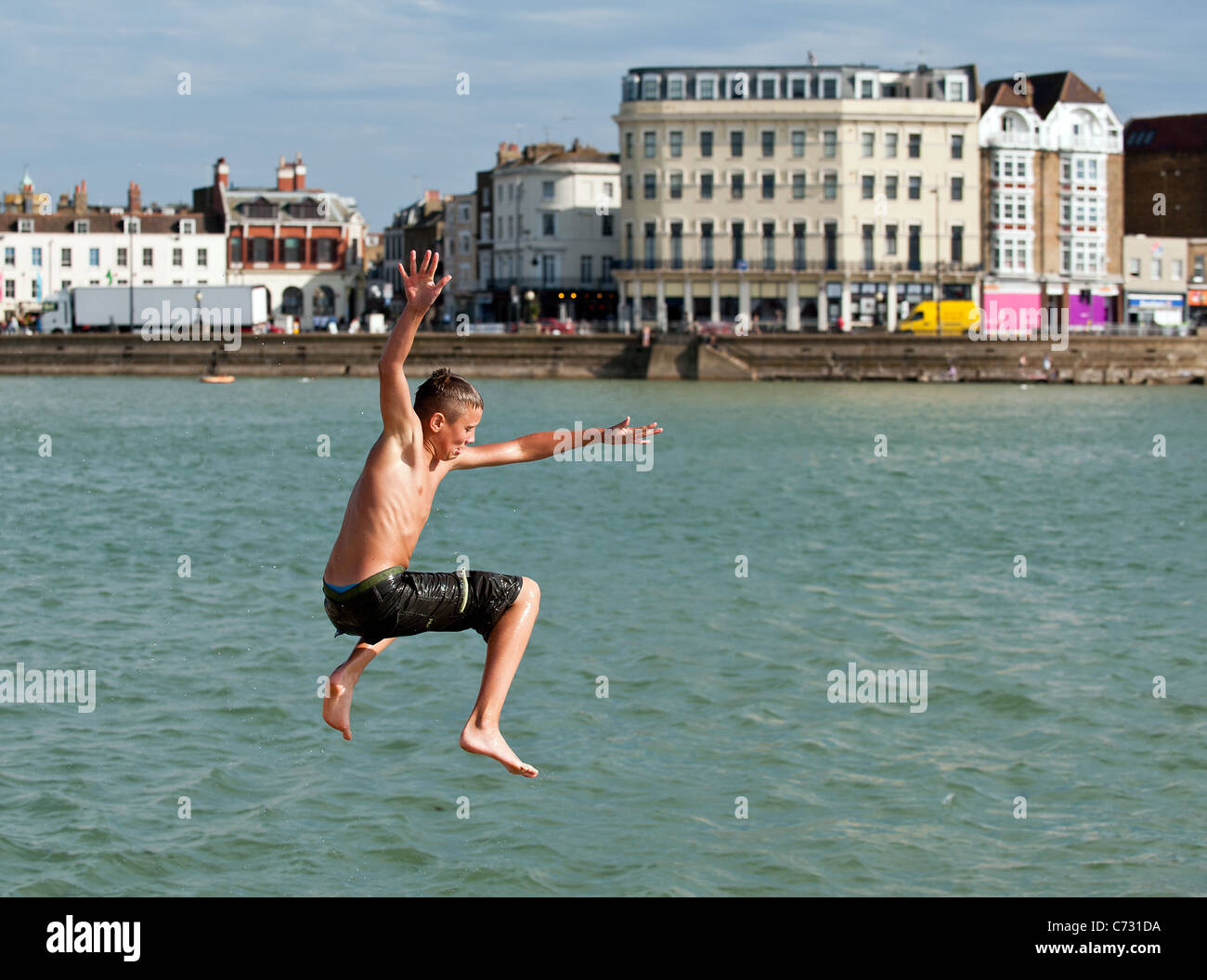 A boy tombstoning off the harbour at Margate in Kent. - Stock Image