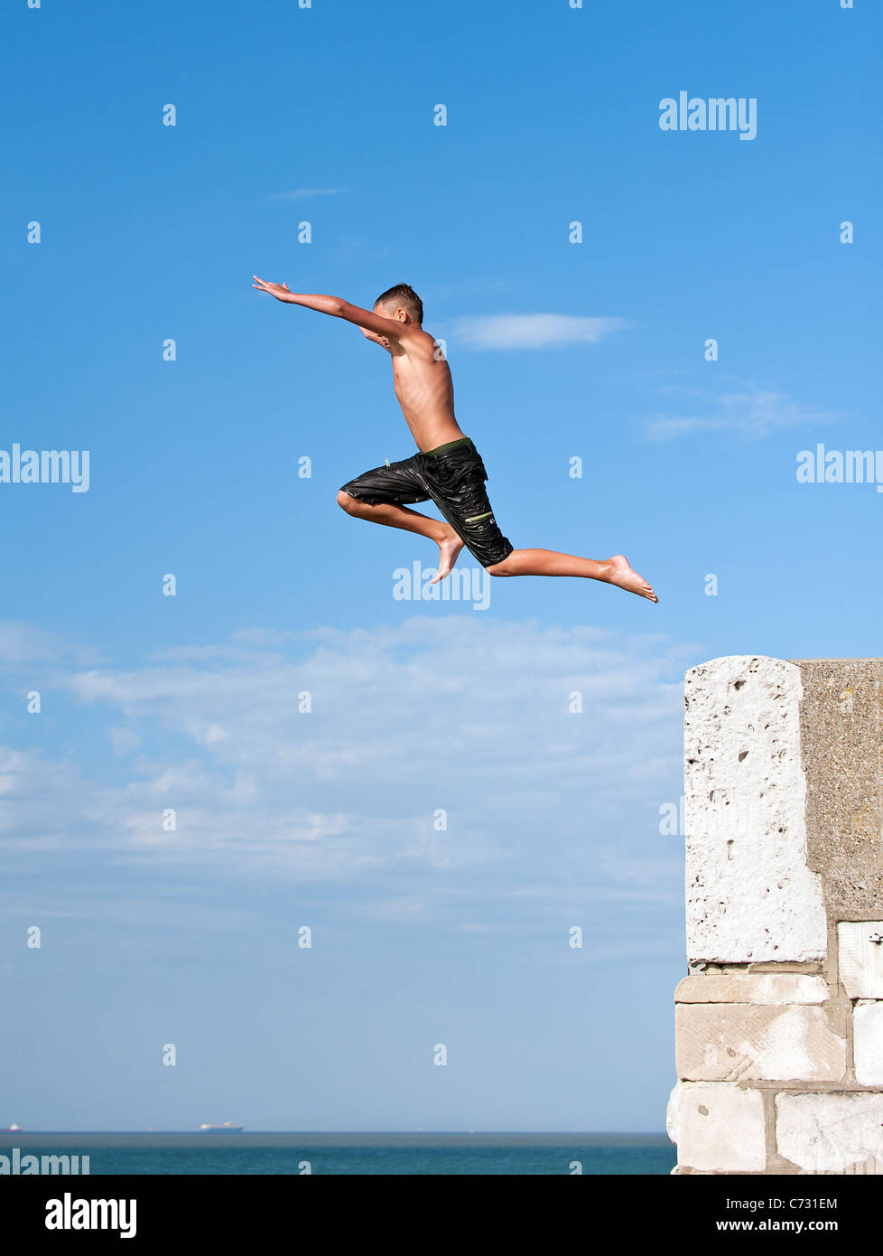 A boy tombstoninbg off the harbour arm in Margate. - Stock Image