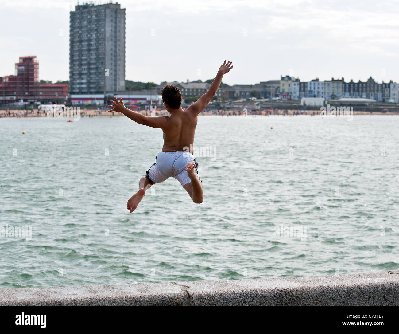 A boy tombstoning off the end of the harbour arm in Margate. - Stock Image