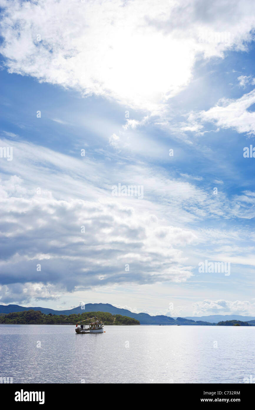 Fishing boat on the loch viewed from Luss on the west bank of Loch Lomond, Argyll and Bute, Scotland, UK - Stock Image