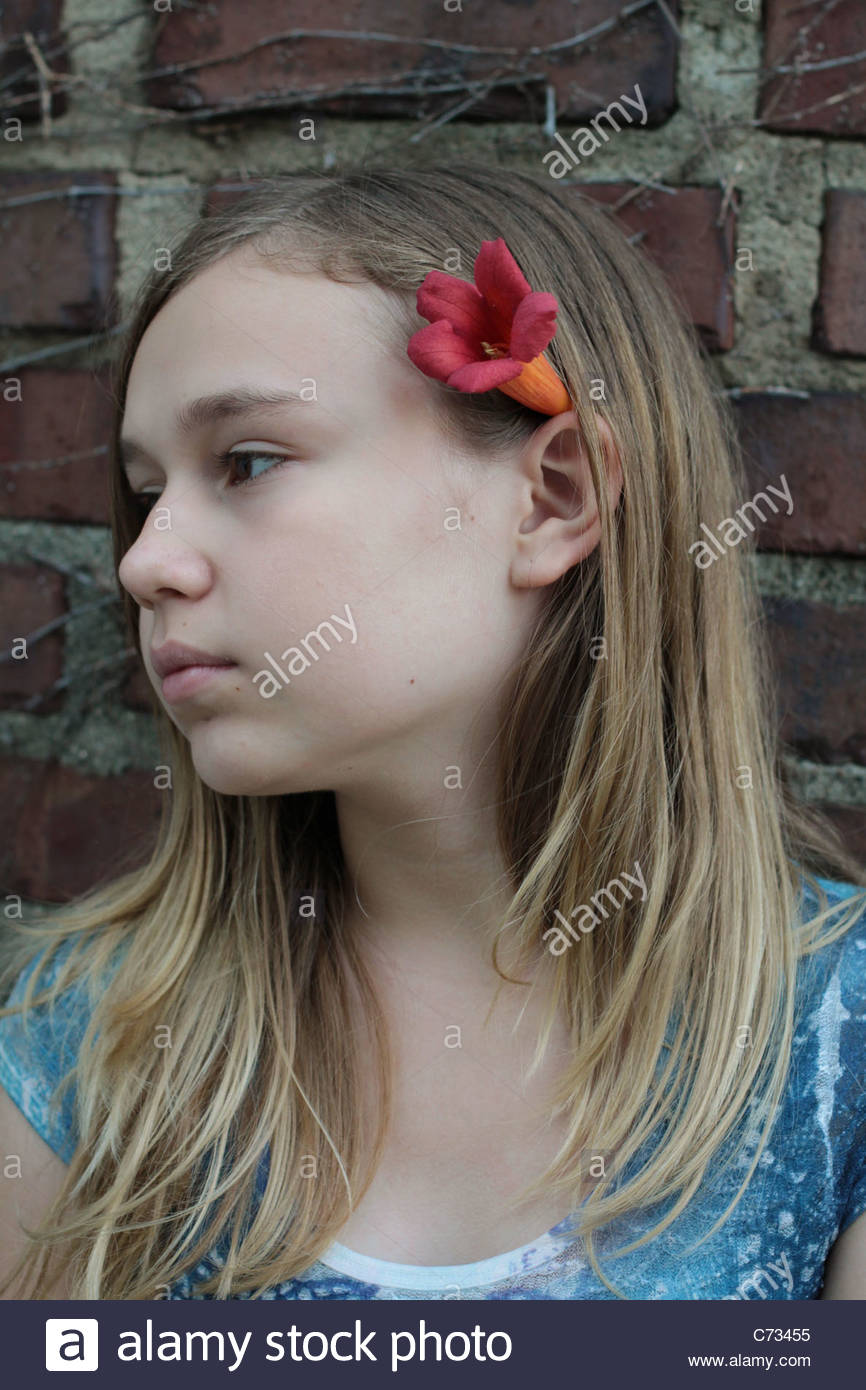 A 12 year old girl with a flower in her hair. - Stock Image
