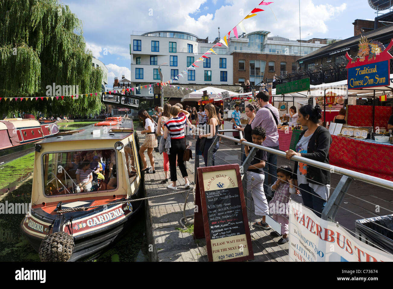 Narrowboats for canal trips and food stalls at Camden Lock, North London, England, UK - Stock Image