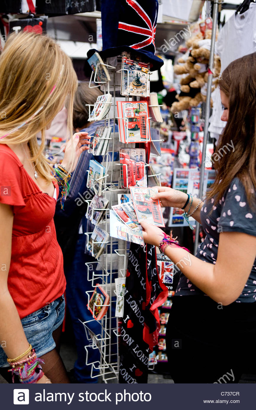 Two teenage girls looking at postcards in a souvenir shop - Stock Image