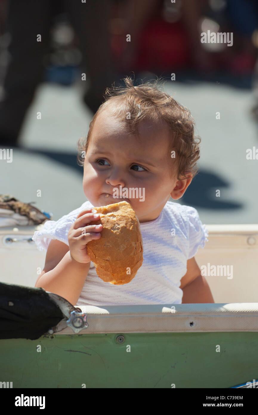Baby eating bread in vintage Pram - Stock Image