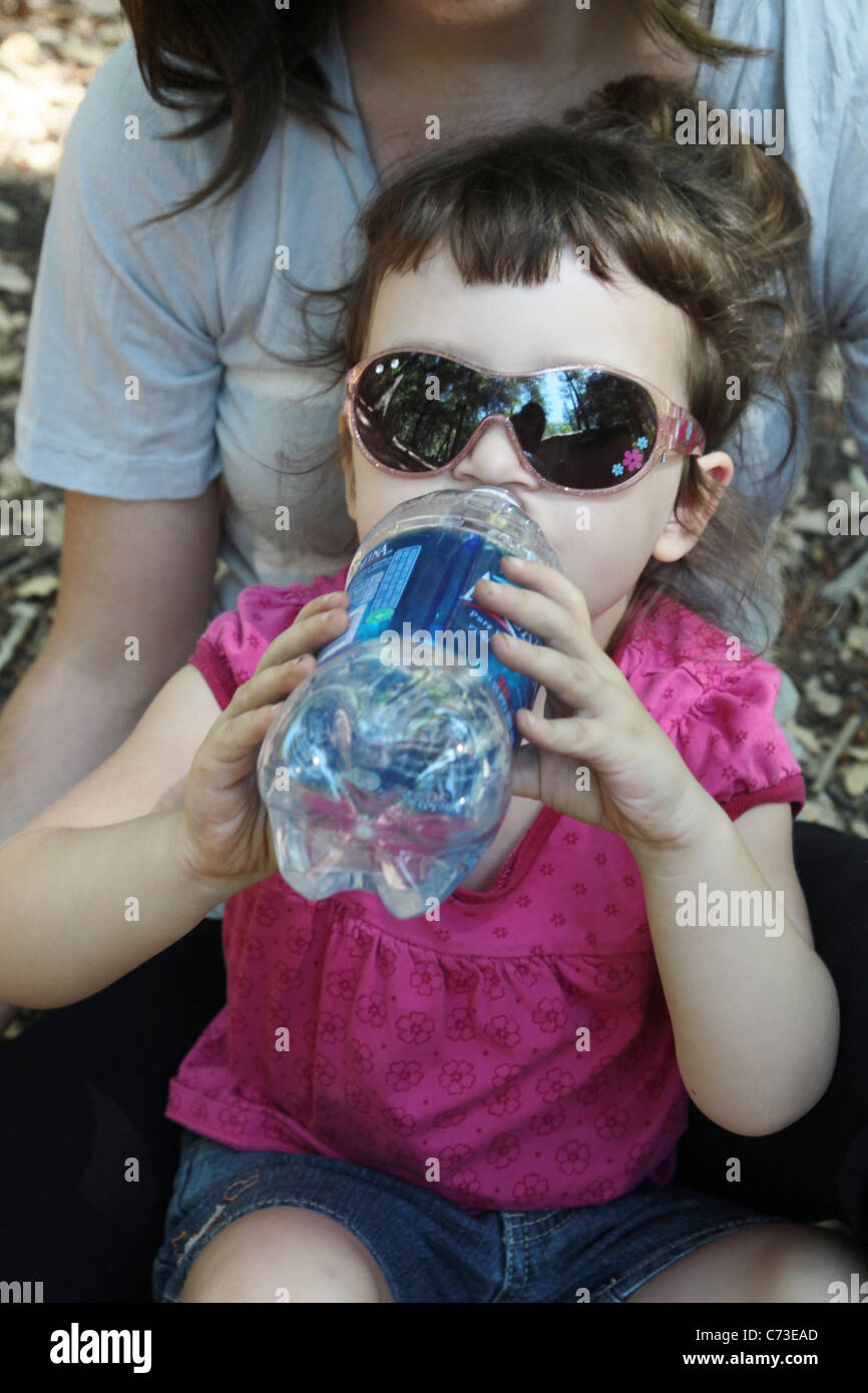 A young girl drinking water from a plastic bottle. - Stock Image