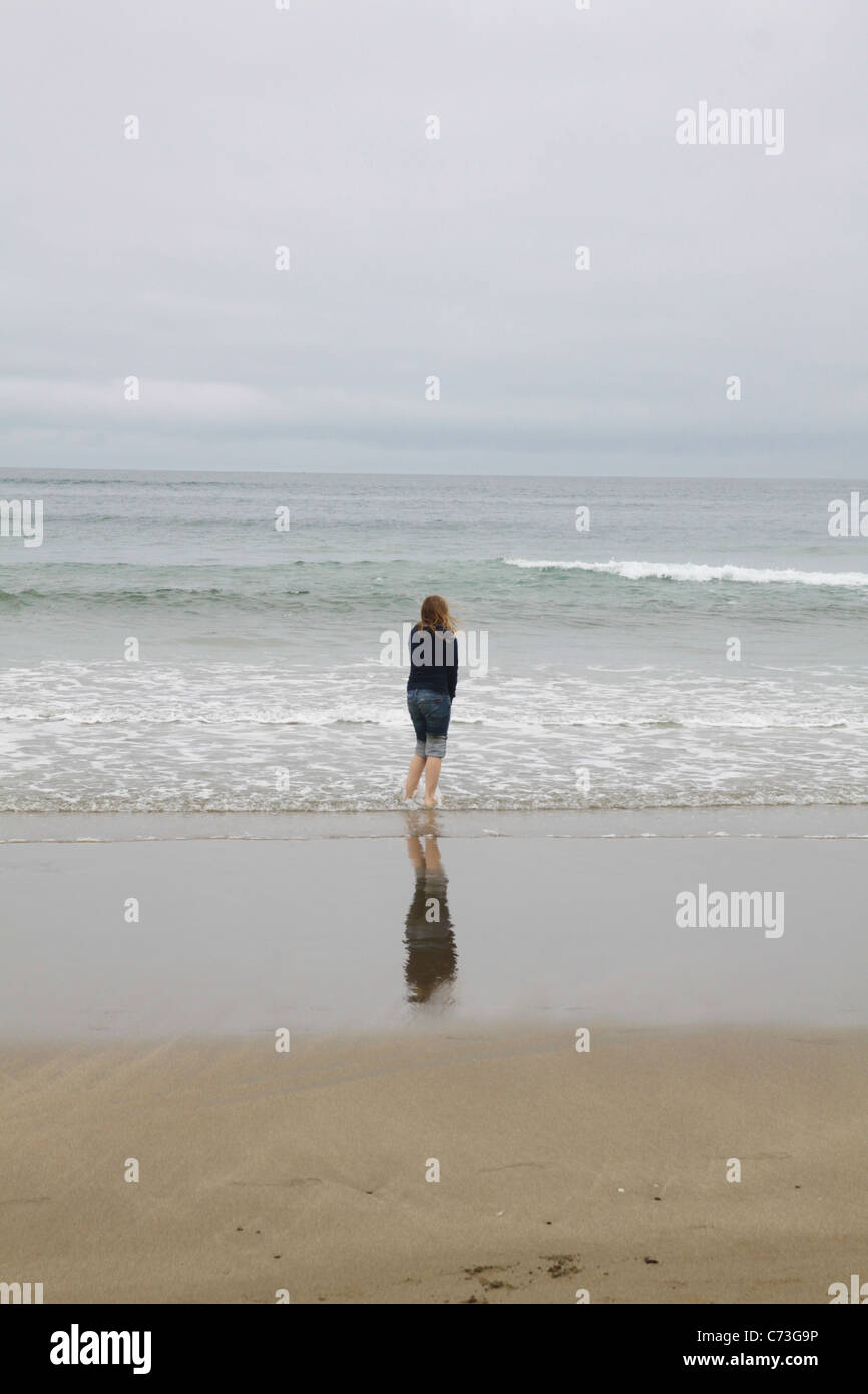 https://c8.alamy.com/comp/C73G9P/a-girl-standing-at-the-edge-of-the-water-at-the-ocean-C73G9P.jpg