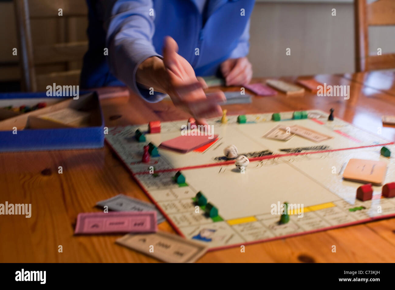 Woman shaking the dice, Monopoly board game, German version, detail, blurred, play money, Germany - Stock Image
