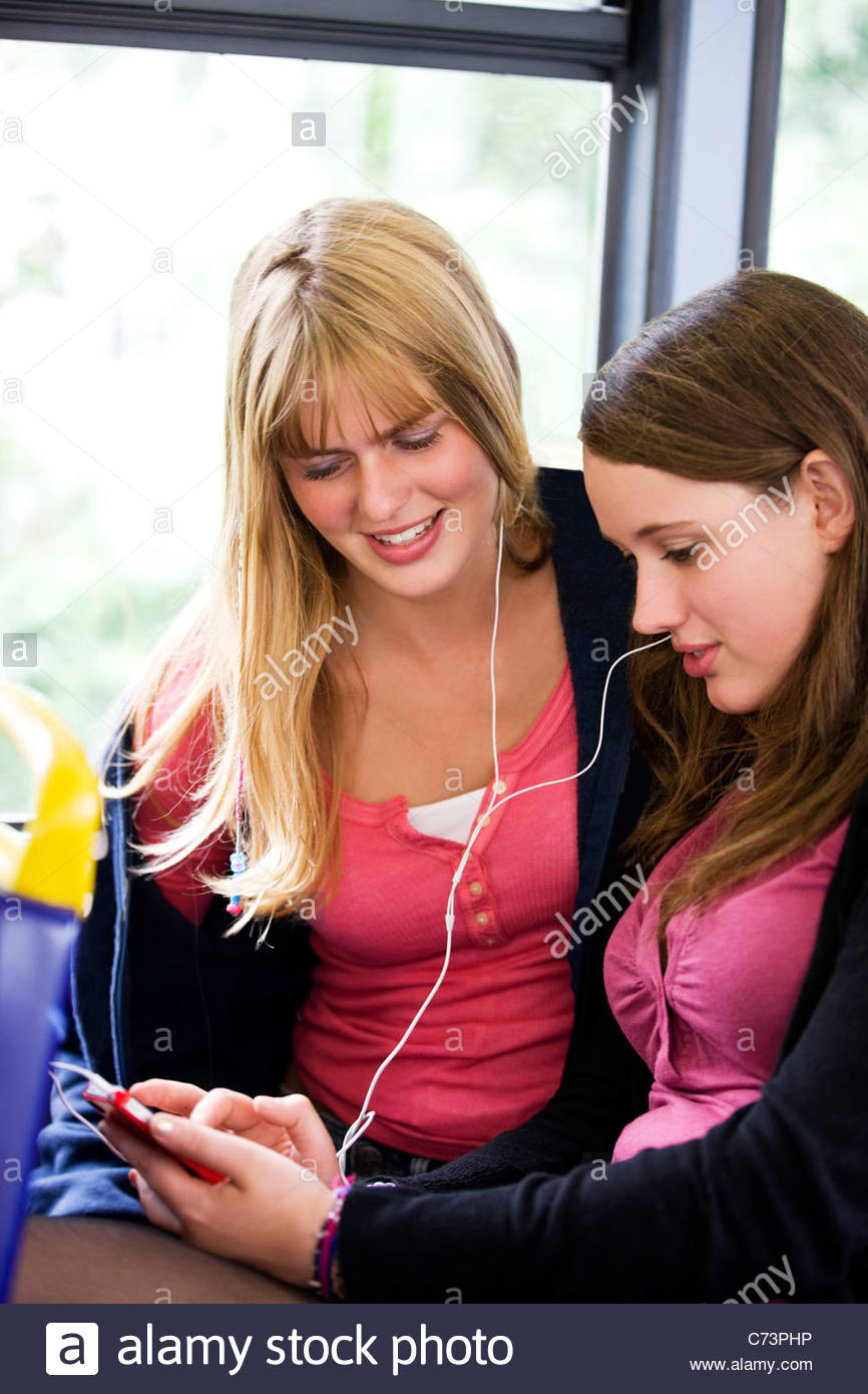 Two teenage girls sitting on a bus, listening to music - Stock Image
