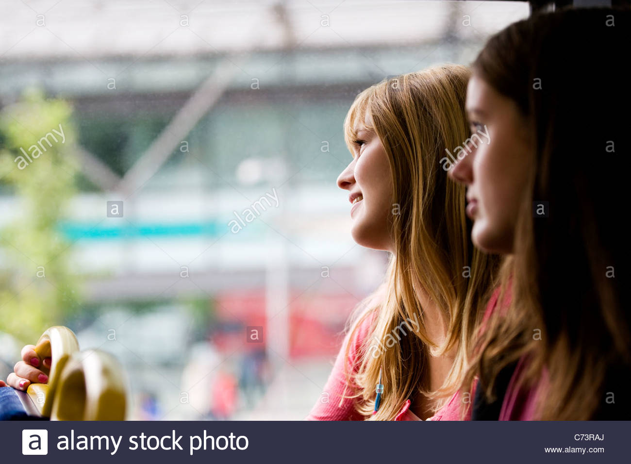 Two teenage girls sitting on a bus, one girl looking out of the window - Stock Image