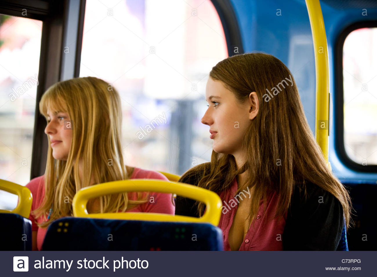 Two teenage girls sitting on a bus, looking out of the window - Stock Image