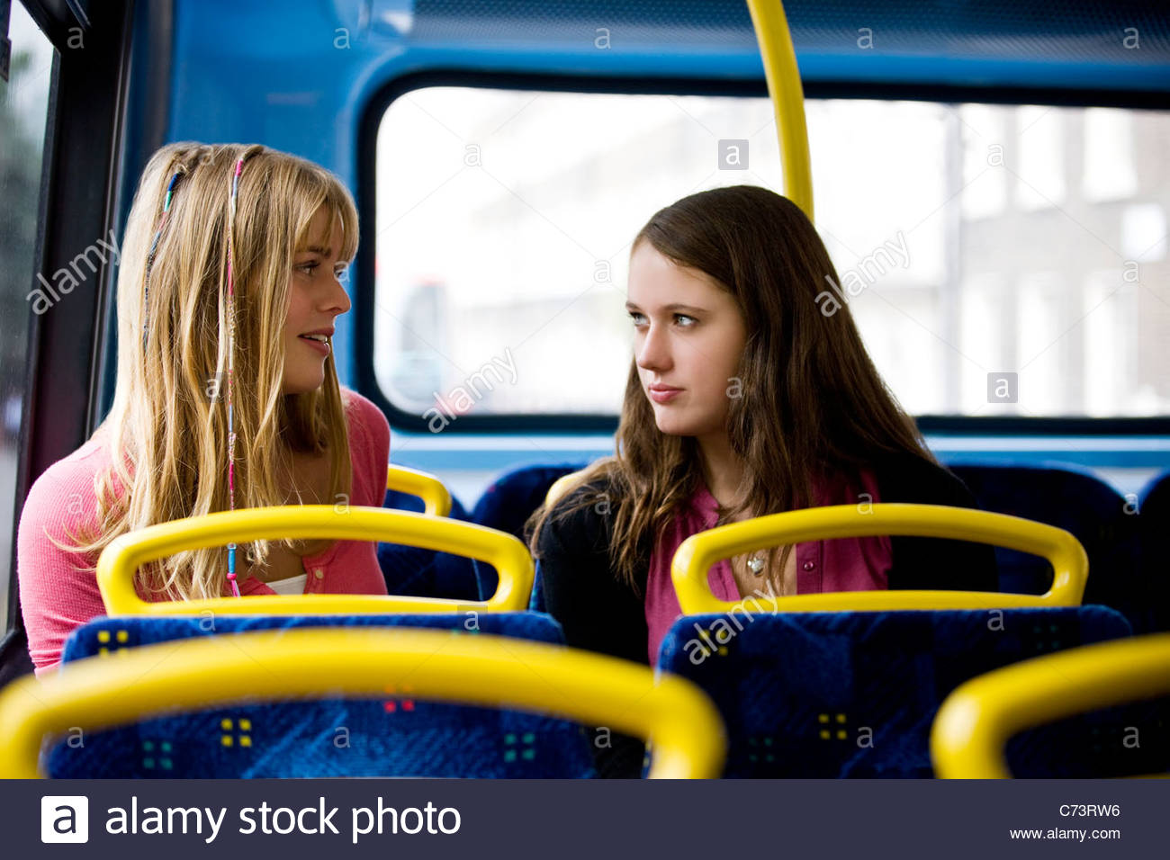 Two teenage girls sitting on a bus, having a conversation Stock Photo