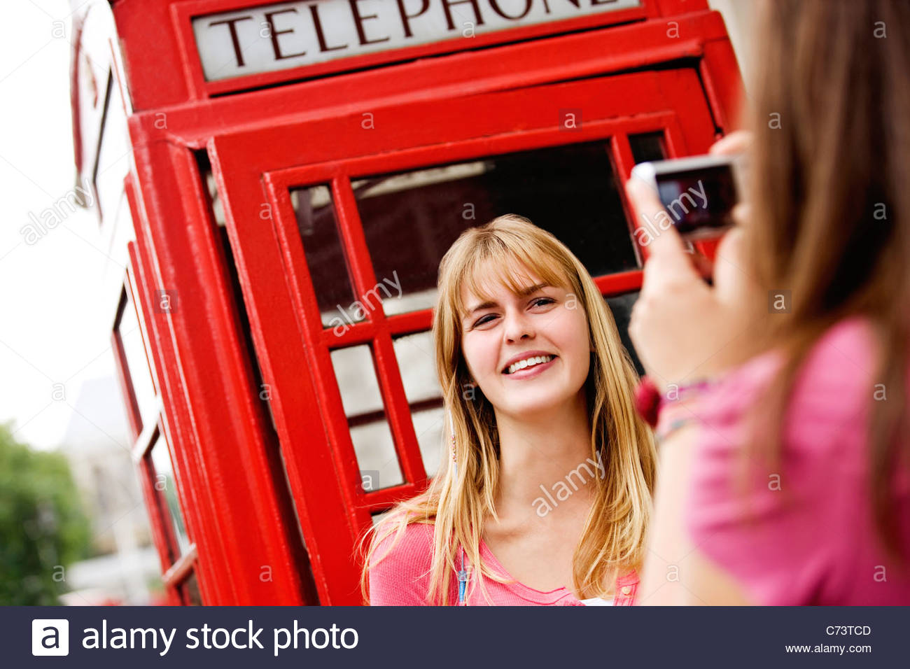 A teenage girl taking a photograph of her friend in front of a telephone box - Stock Image