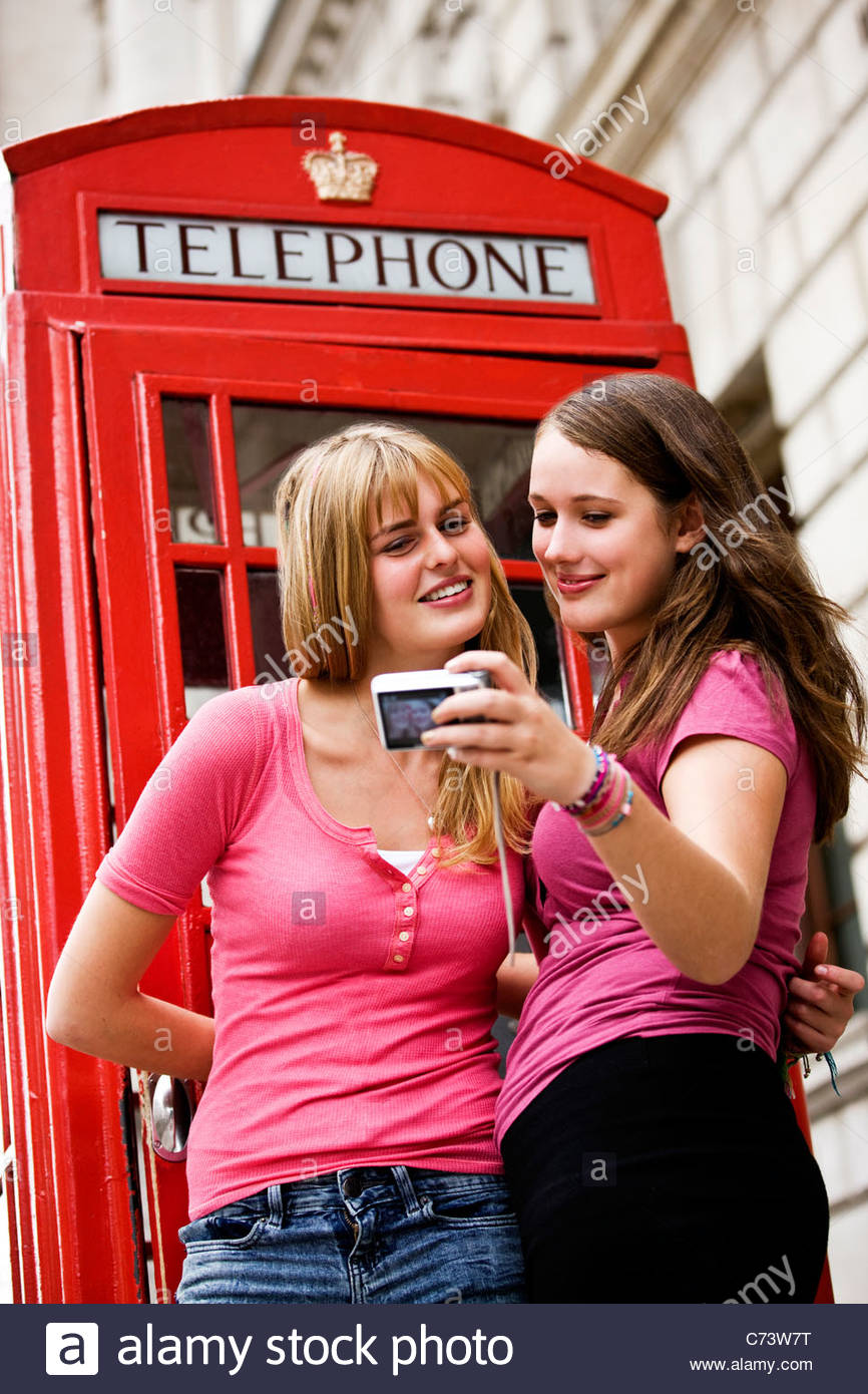 Two teenage girls taking a photograph of themselves in front of a telephone box - Stock Image