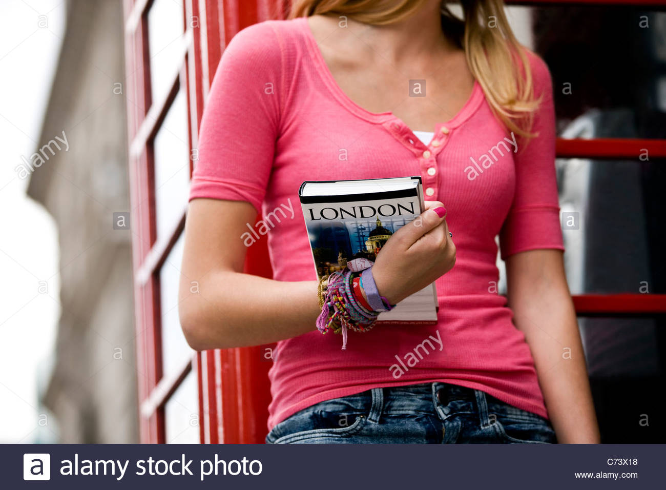A teenage girl holding a London guidebook - Stock Image
