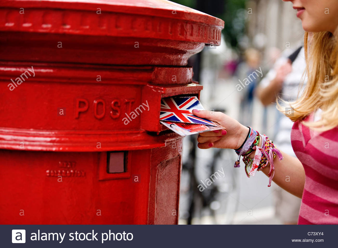 A teenage girl putting postcards into a red letterbox - Stock Image