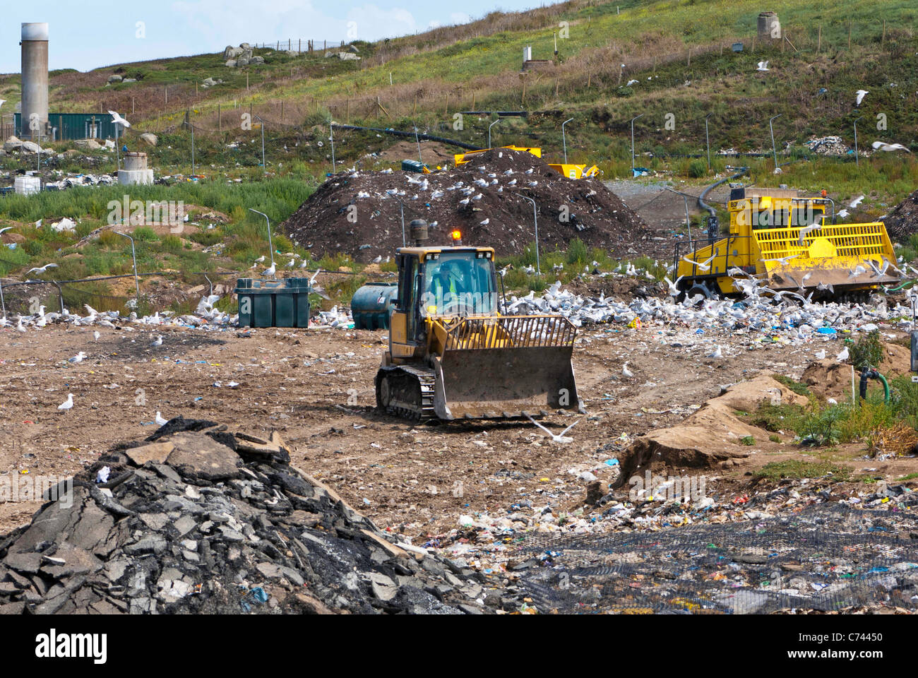 Bulldozer working in landfill site and seagulls with methane gas burner in the background. - Stock Image