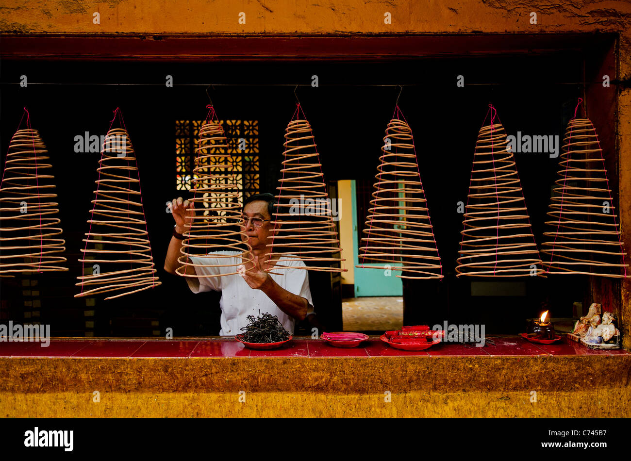 man lighting incense in chinese temple vietnam - Stock Image