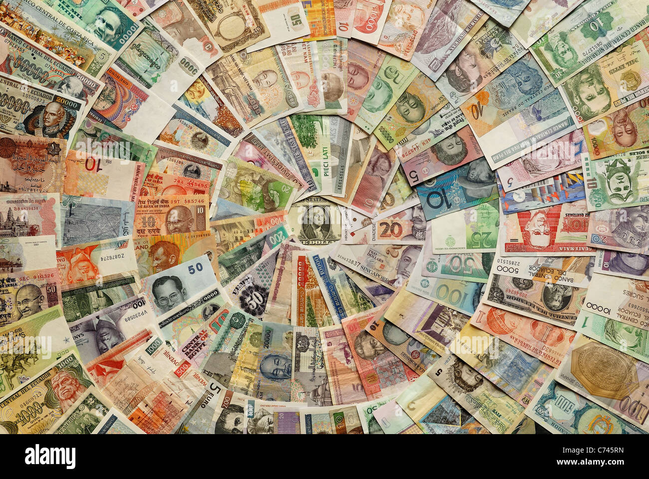 Bills in different currencies ordered in circles around the central dollar. - Stock Image