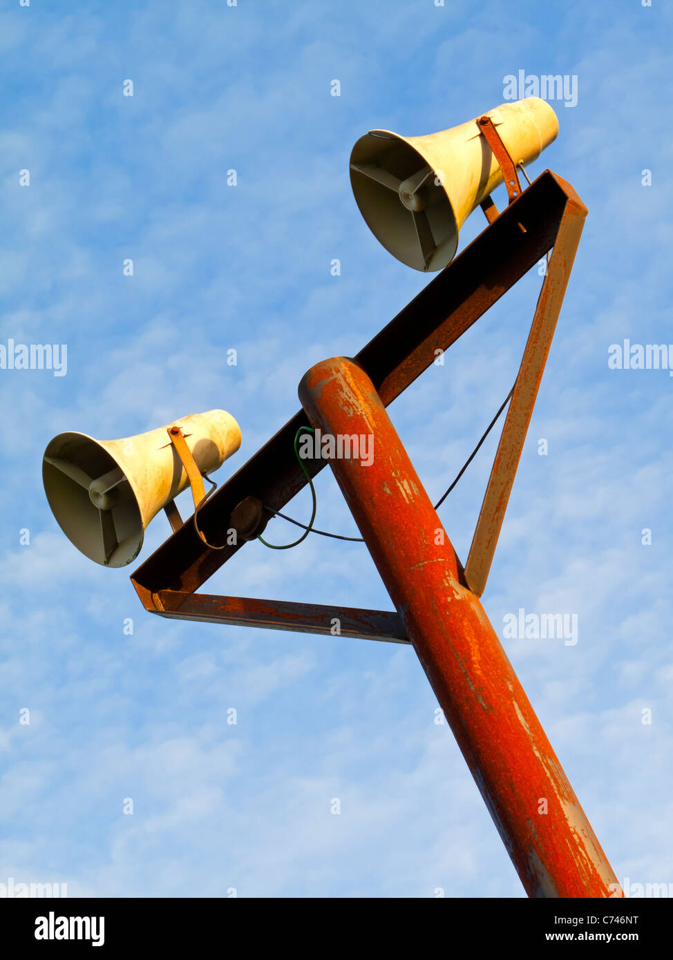 Pair of public address system loudspeakers on a pole with blue sky behind - Stock Image