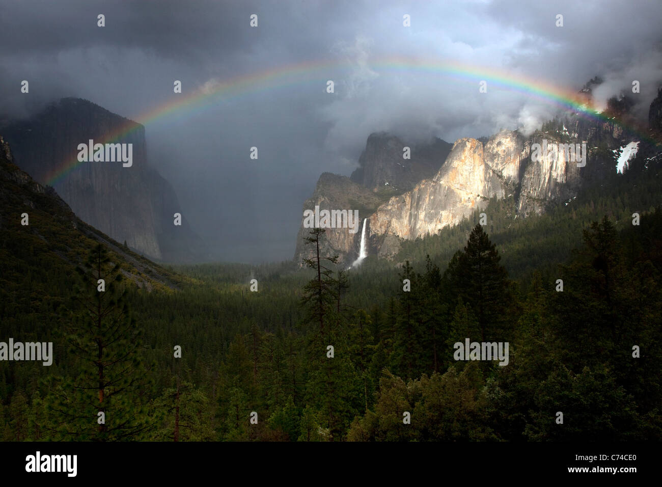 A beautiful rainbow appears over Yosemite Valley following a rain storm. - Stock Image