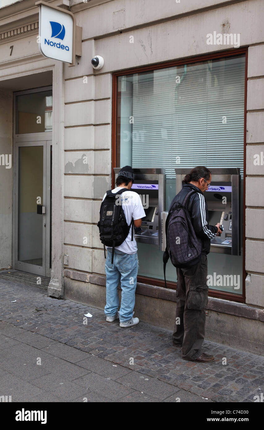 Two persons getting cash from the automatic teller machines at Nordea Bank, Strøget, Copenhagen, Denmark - Stock Image