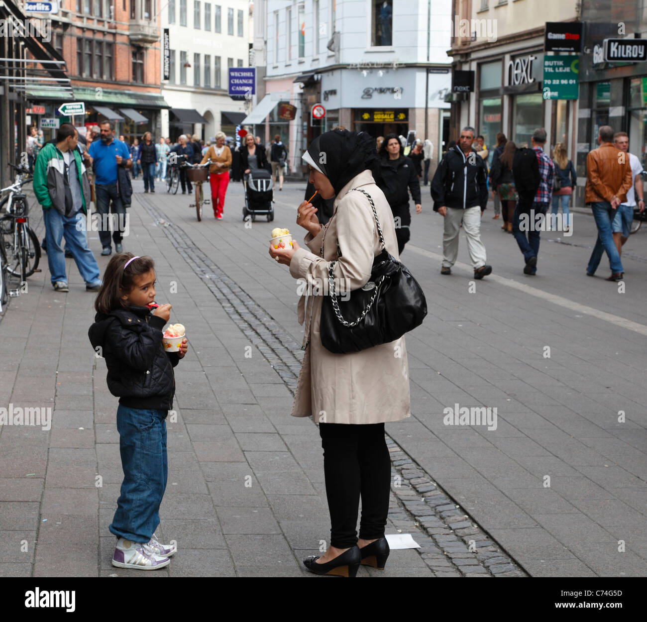A young immigrant mother and her young daughter eating ice-cream on the pedestrian and shopping street Strøget - Stock Image
