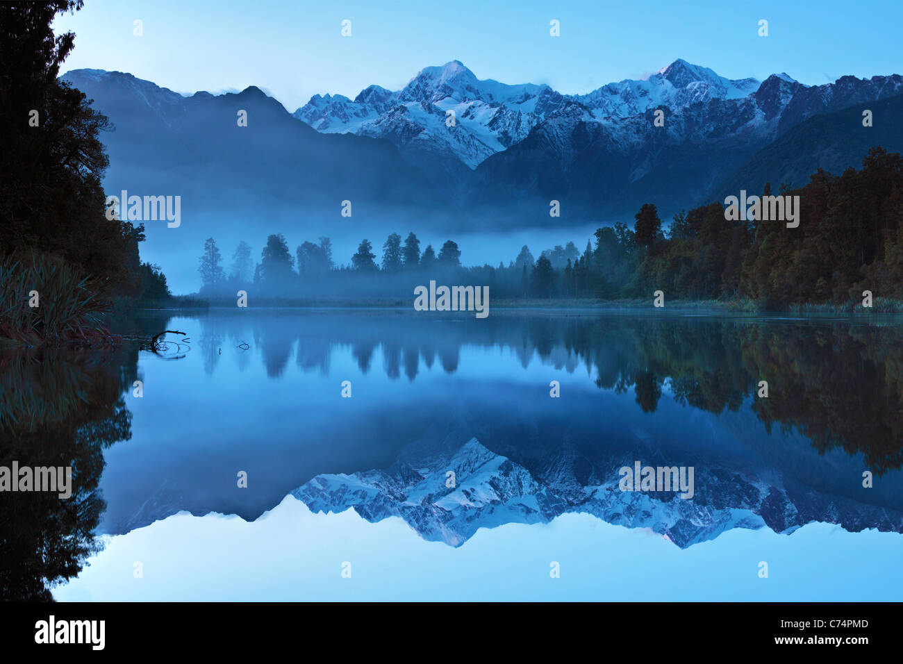 Reflection of Mt Cook (Aoraki) and Mt Tasman on Lake Matheson near Fox Glacier in New Zealand - Stock Image