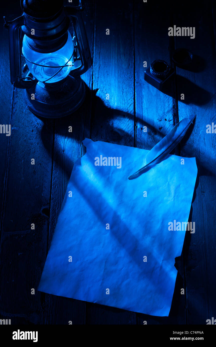 Blank Paper Sheet with Feather, Lantern and Ink at Night - Stock Image