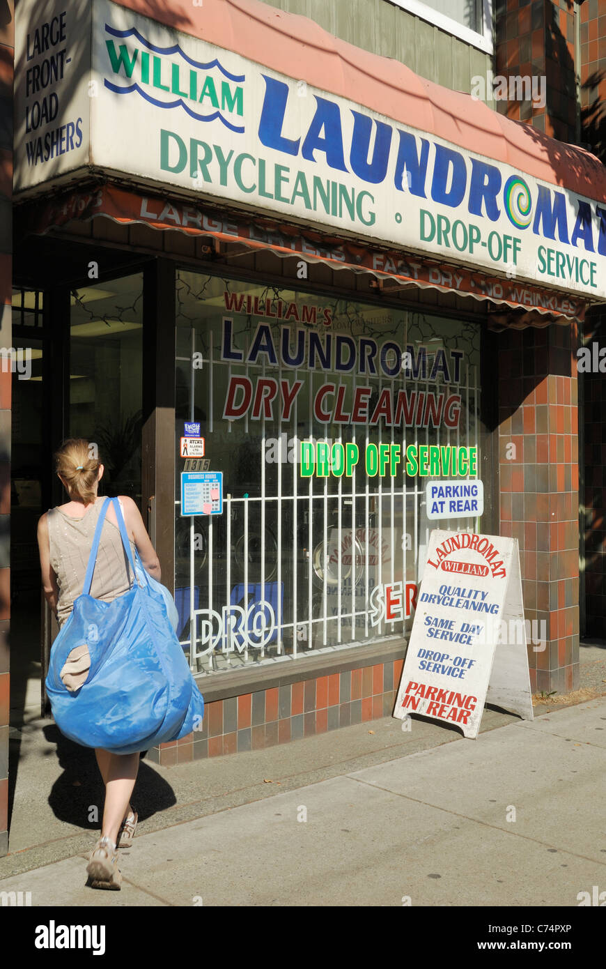 Female customer carrying her laundry entering a public laundromat located on Commercial Drive, Vancouver - Stock Image