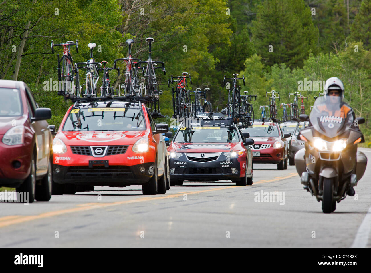 Team support vehicles escort professional cyclists as they race up Independence Pass in Stage 2 of the USA Pro Cycling - Stock Image