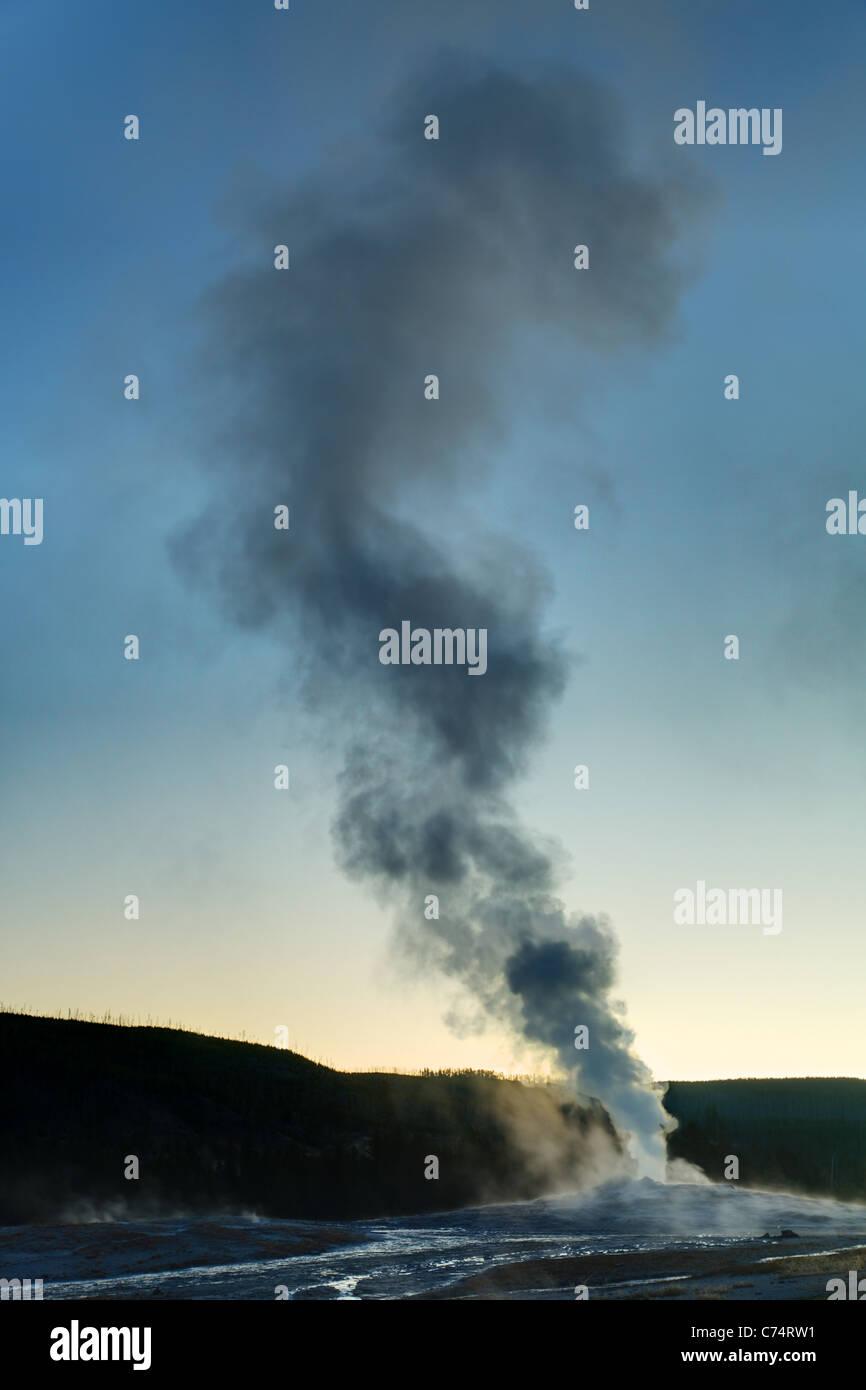 Old Faithful geyser erupting under early morning twilight sky, Yellowstone National Park, Wyoming, USA - Stock Image