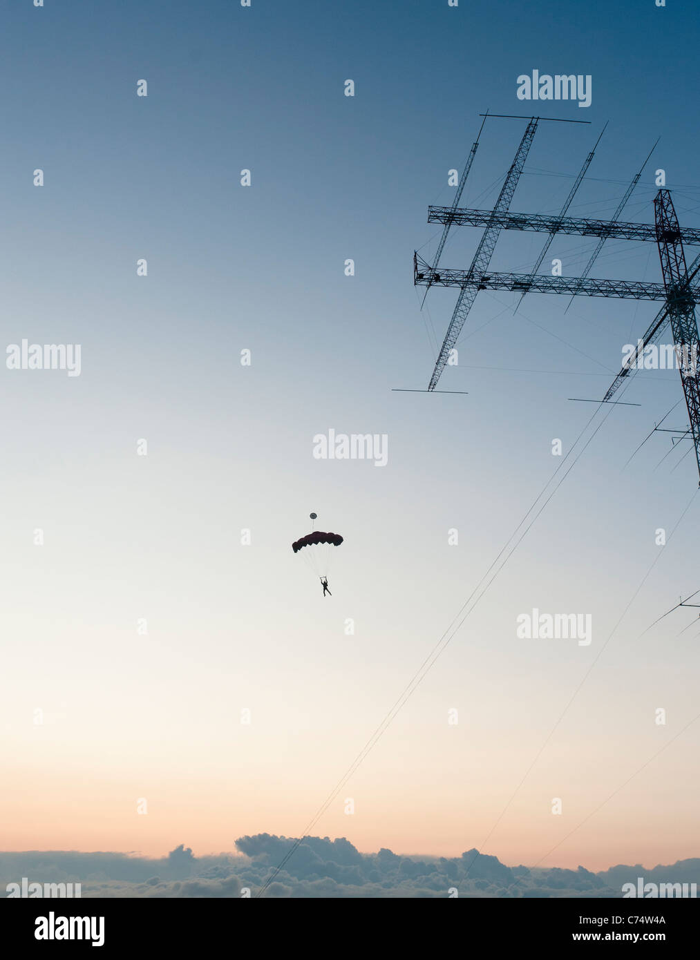 A base jumper jumping from an radio amateur antenna in the midnight sun. Radio Arcala, Oulu, Finland - Stock Image