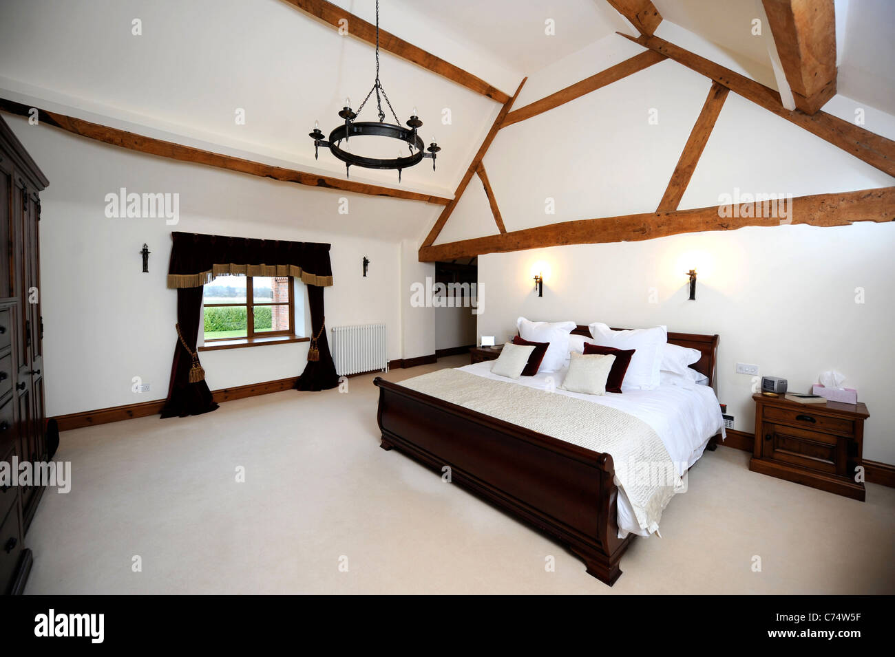 Master bedroom with a vaulted ceiling in a converted barn ...