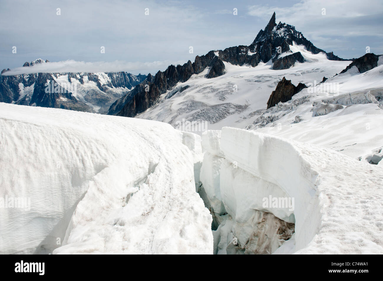 A giant crevasse on the Vallee Blanche, with Dent du Geant in the background. - Stock Image