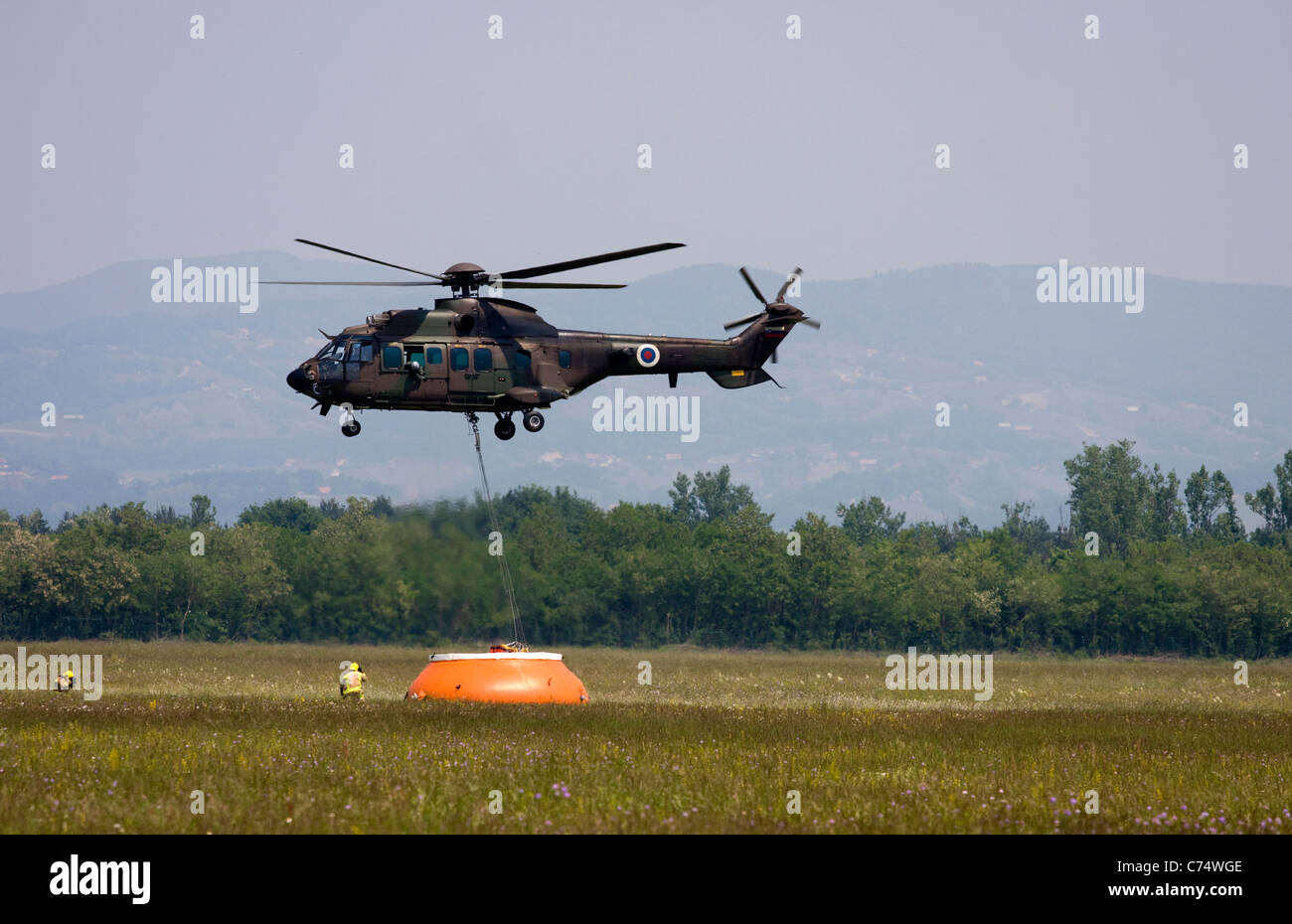 Helicopter floating and picking up water. - Stock Image