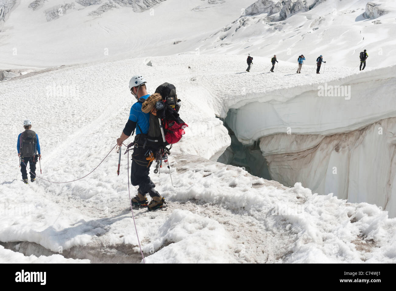 Climbers walking among crevasses on the Vallee Blanche glacier in Chamonix, France - Stock Image