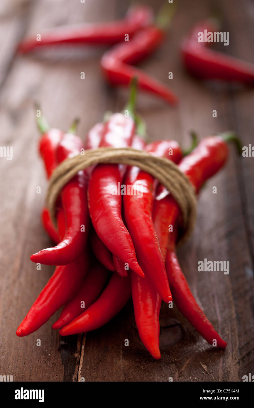 Red Chili Peppers Tied with Rope on Wood - Stock Image