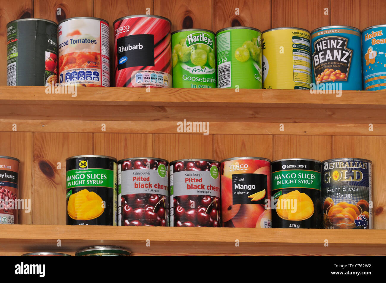 Tins of food on shelves in a kitchen UK - Stock Image