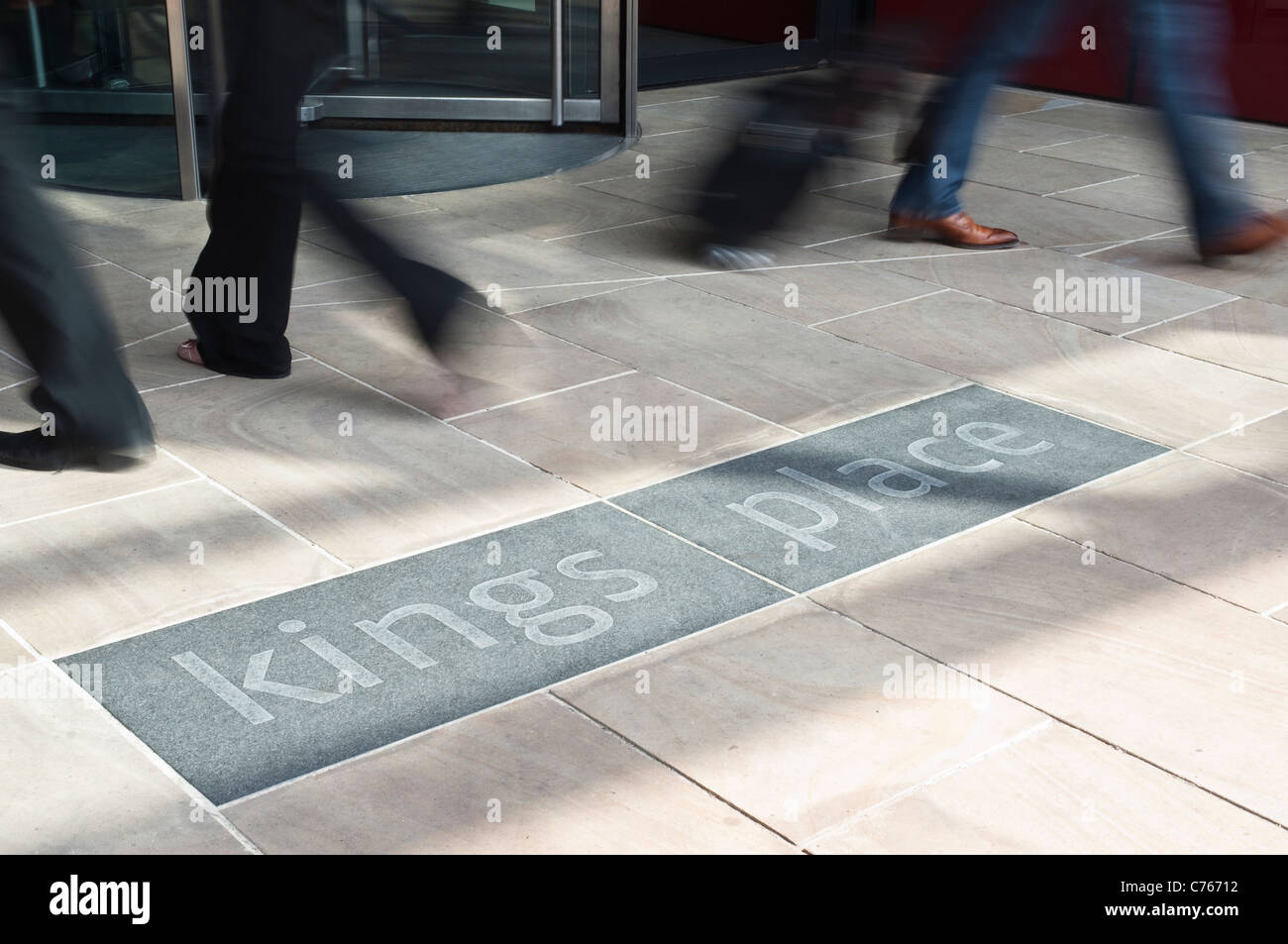 The entrance to Kings Place in London, with revolving doors, the blurred feet of passing people, and the building - Stock Image