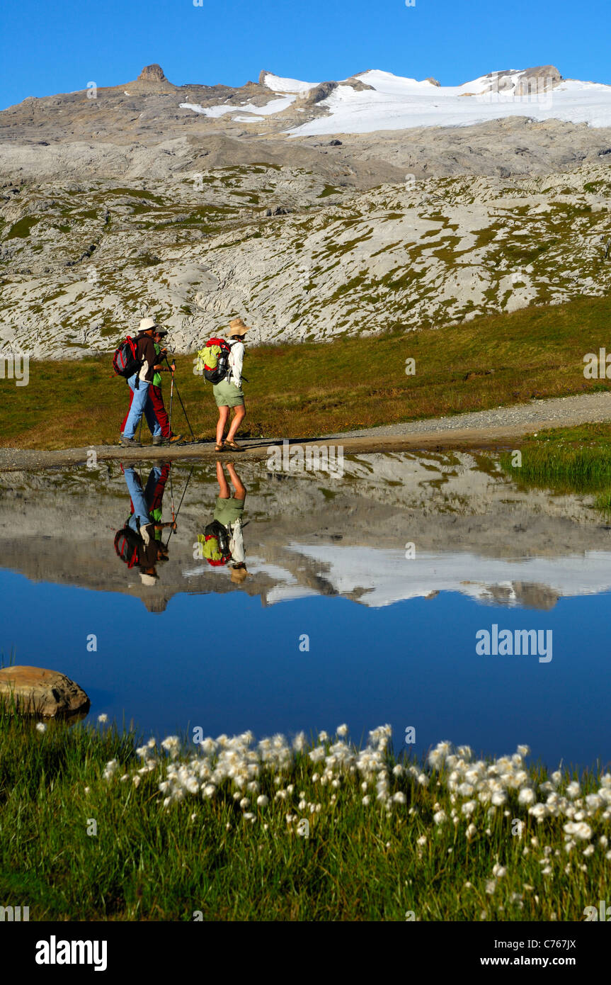 Hikers passing by a small mountain lake at the Sanetsch pass on the way to the Tsanfleuron glacier, Valais, Switzerland - Stock Image