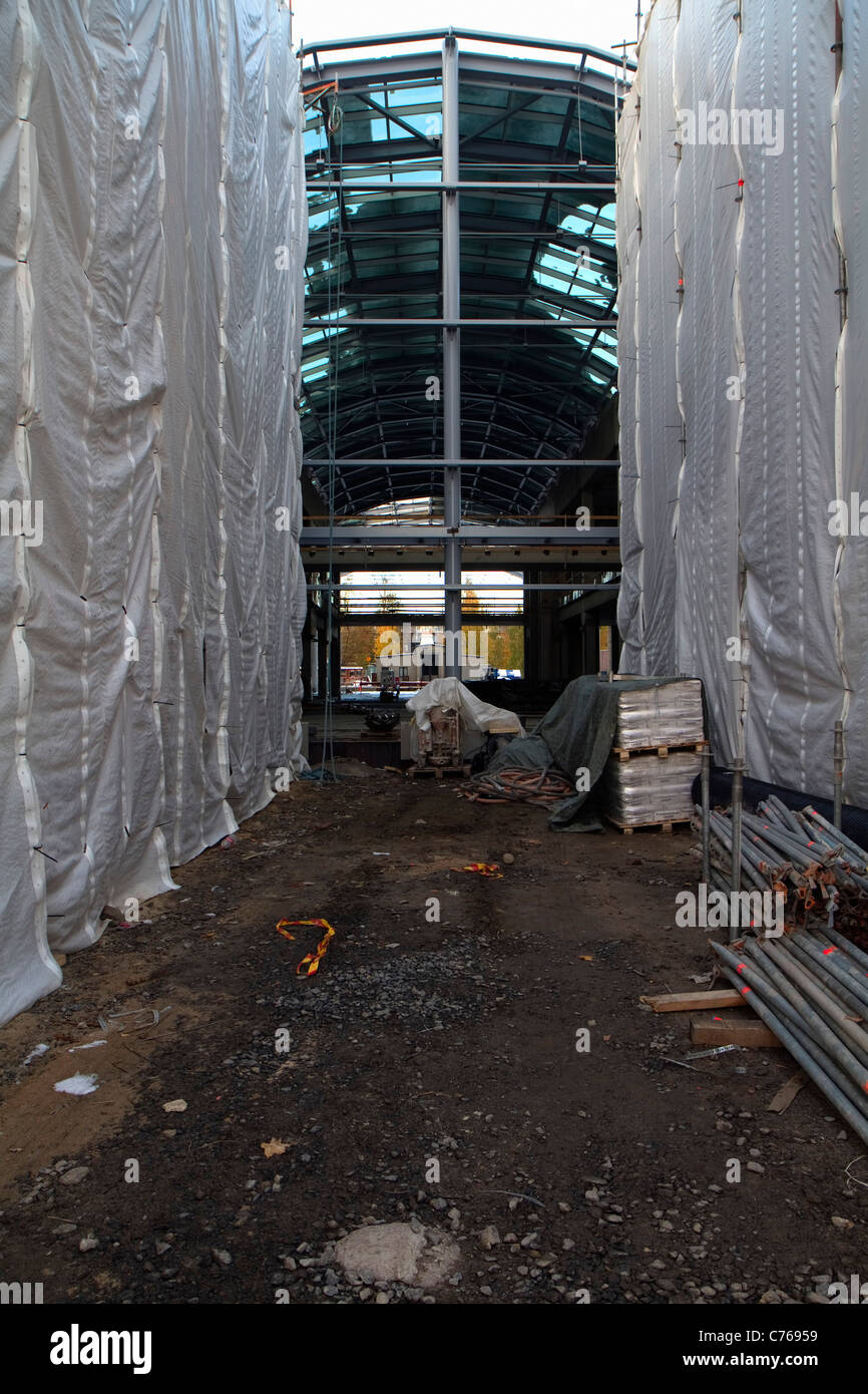 Hanging tarpaulins and glass and steel constructions on a shopping mall construction site. - Stock Image
