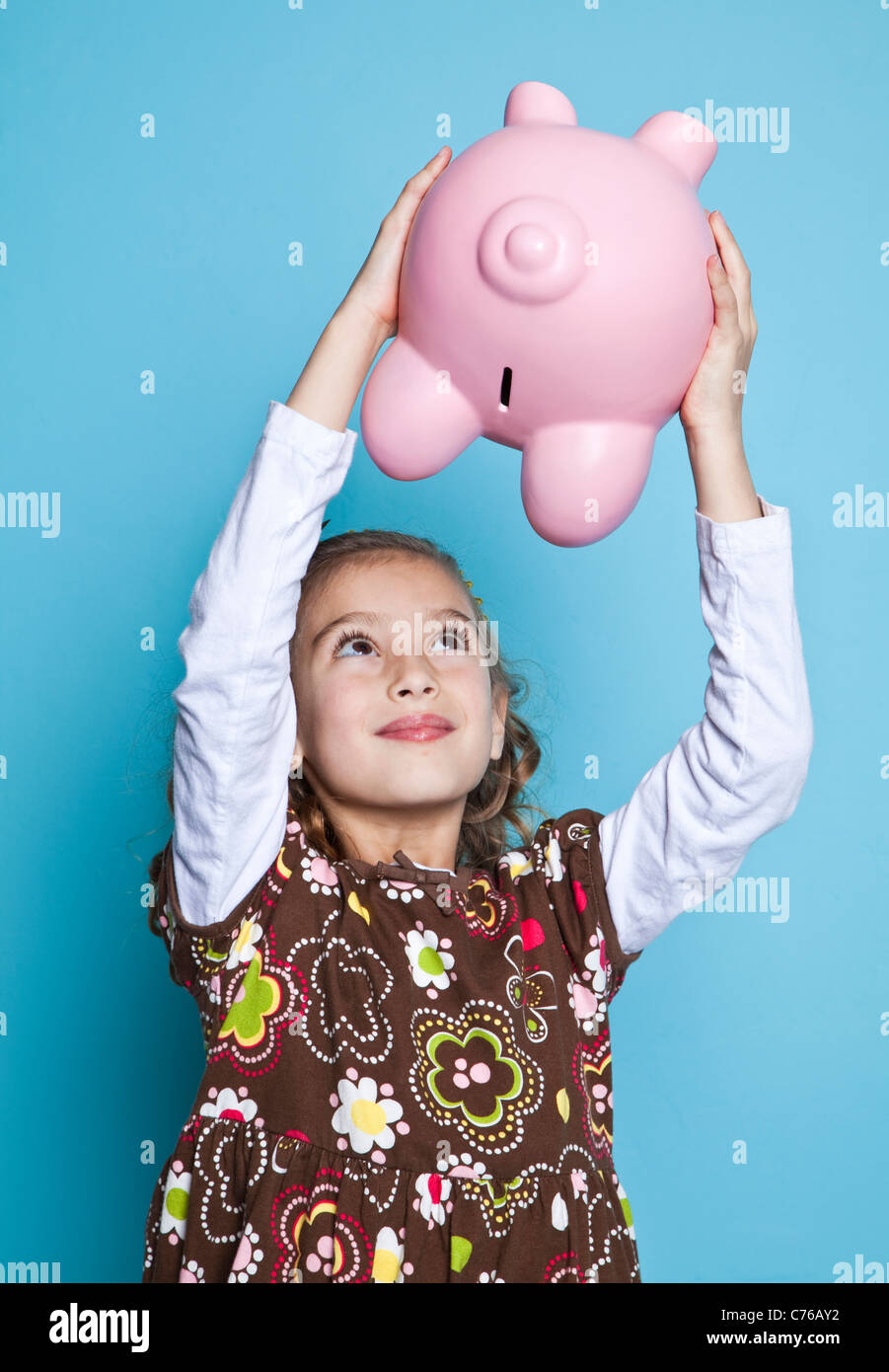 Girl (8-9) holding piggybank, studio shot - Stock Image