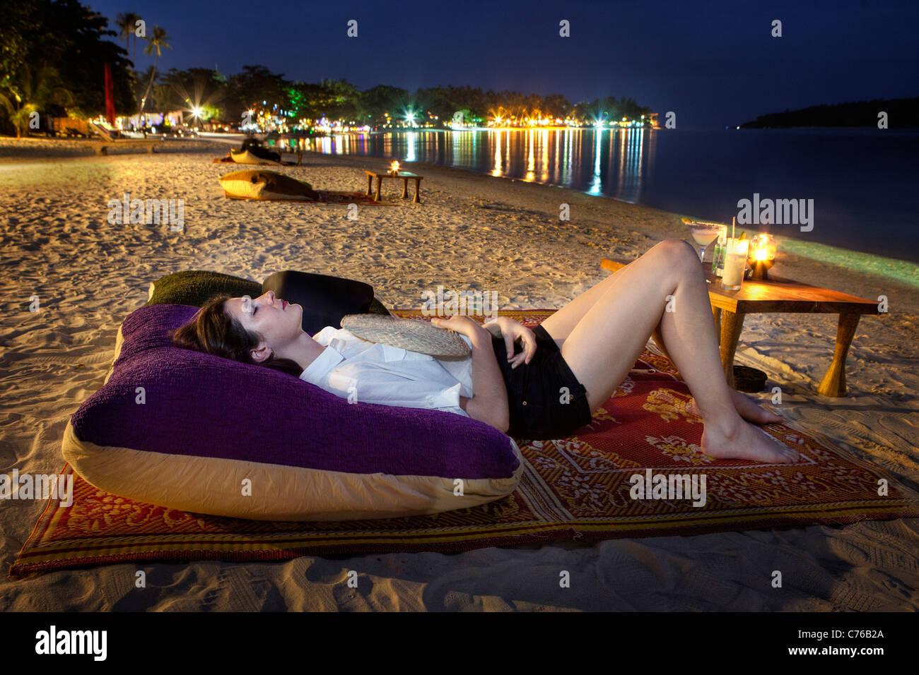Young woman reclining on a cushion on a Thai beach at night (Ko Samui, Thailand) Stock Photo