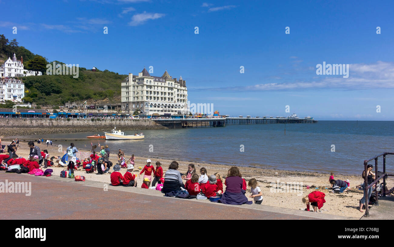A party of school children visit Llandudno beach, with teachers and assistants, sandy bay with small boat, pier Stock Photo